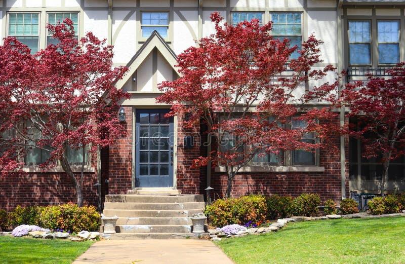 Ingang van het huis van baksteentudor revival met Chinese Esdoornbomen aan beide kanten van de deur en de afbrokkelende cementpor royalty-vrije stock afbeelding