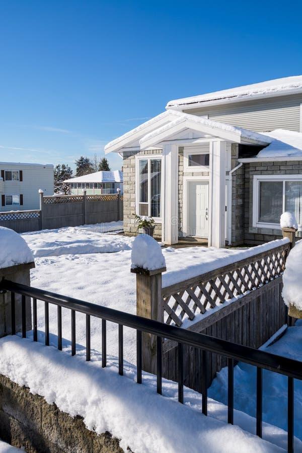 Ingang van nieuw modieus familiehuis in sneeuw bij de wintertijd in Canada stock afbeelding
