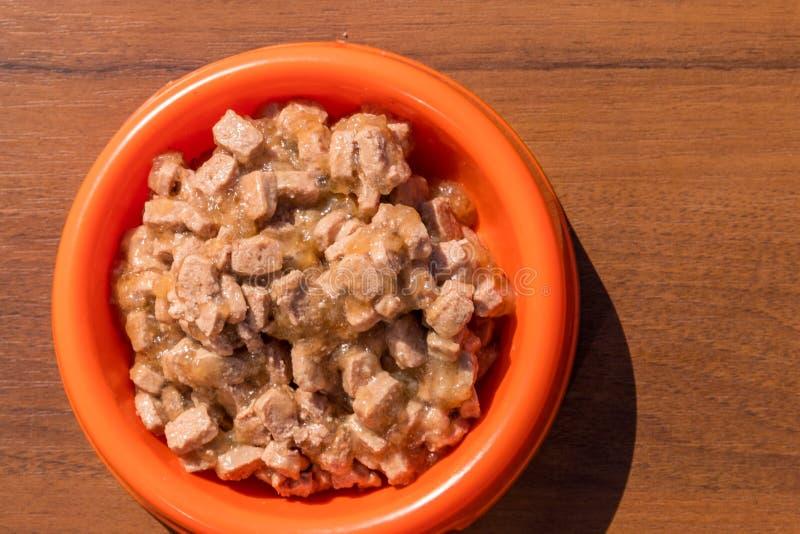 Ingeblikt voedsel voor katten of honden in oranje plastic kom stock afbeeldingen