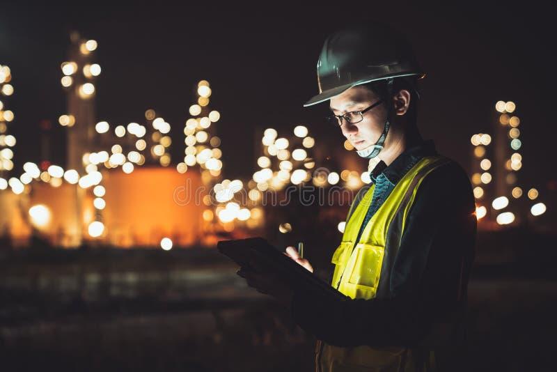 Ingegnere asiatico dell'uomo facendo uso della compressa digitale che funziona spostamento a tarda notte alla raffineria dell'oli immagini stock