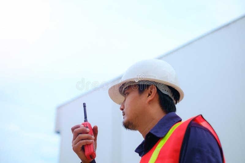 Ingegnere asiatico nel casco uniforme e bianco di sicurezza facendo uso del walkie-talkie sul fondo vago della pianta di industri immagine stock