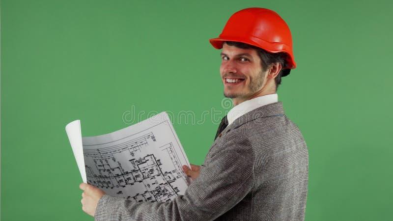 Ingegnere barbuto bello che sorride alla macchina fotografica mentre esaminano blueprints immagine stock libera da diritti