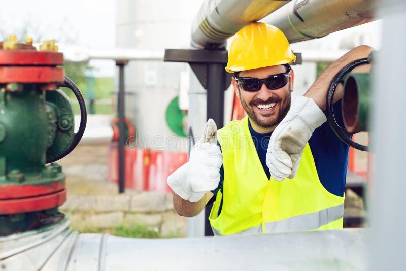 Ingegnere che lavora dentro la raffineria del gas e del petrolio immagini stock