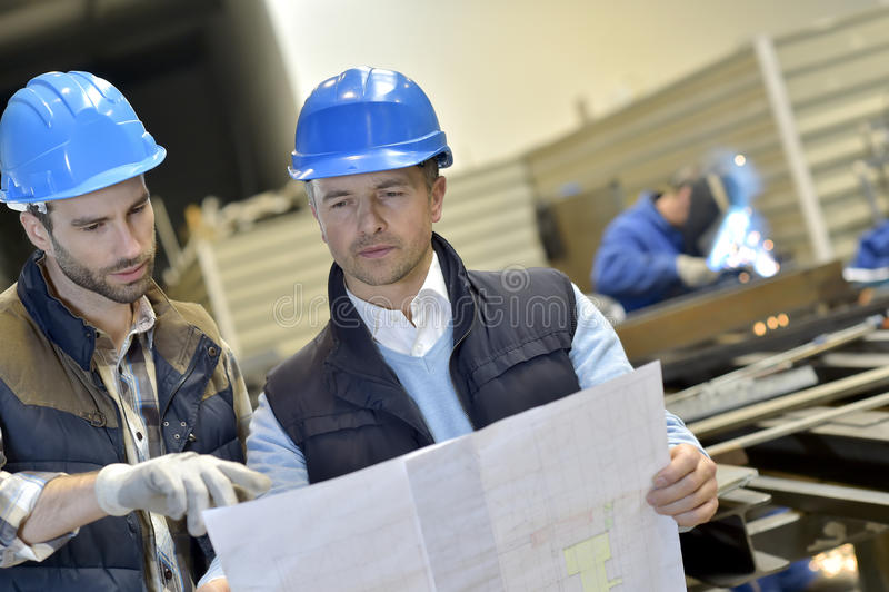 Ingegnere con il lavoratore meccanico in una fabbrica metallurgica immagine stock libera da diritti