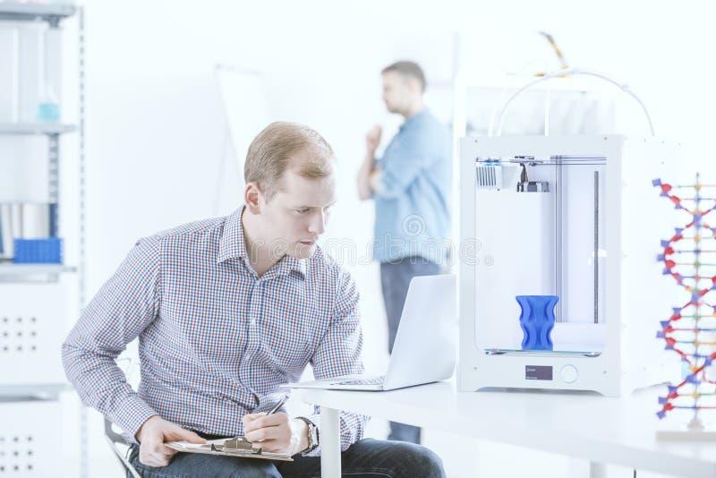 Ingegnere con la stampante di prova del computer portatile immagine stock libera da diritti