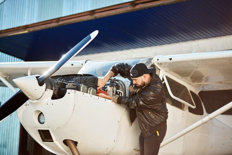Ingegnere del meccanico che ispeziona le costruzioni monomotrici leggere dell'aeroplano dell'elica immagini stock