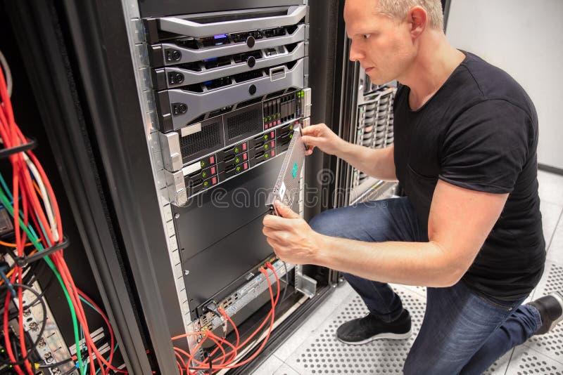 Ingegnere dell'IT che lavora con il server in centro dati immagine stock