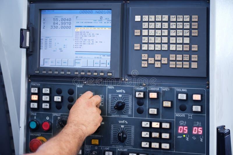 Ingegnere della fabbrica che controlla e che preme il bottone importante di tecnologia al pannello di controllo fotografie stock