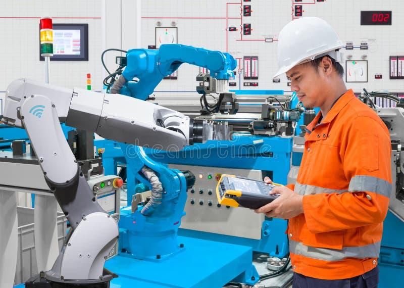 Ingegnere di manutenzione che programma robot automatizzato all'industria 4 fotografie stock
