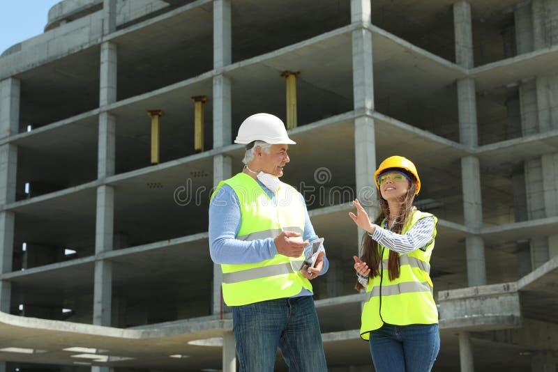 Ingegnere e caporeparto professionisti con la compressa in attrezzatura di sicurezza al cantiere fotografia stock