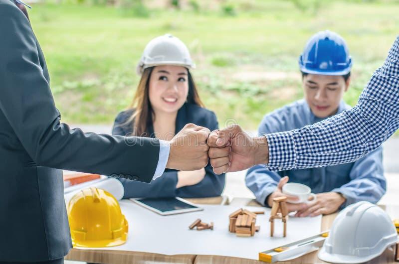 Ingegnere e stretta di mano dell'uomo d'affari, lavoro di squadra fra gli ingegneri di costruzione professionisti dopo il progett fotografia stock