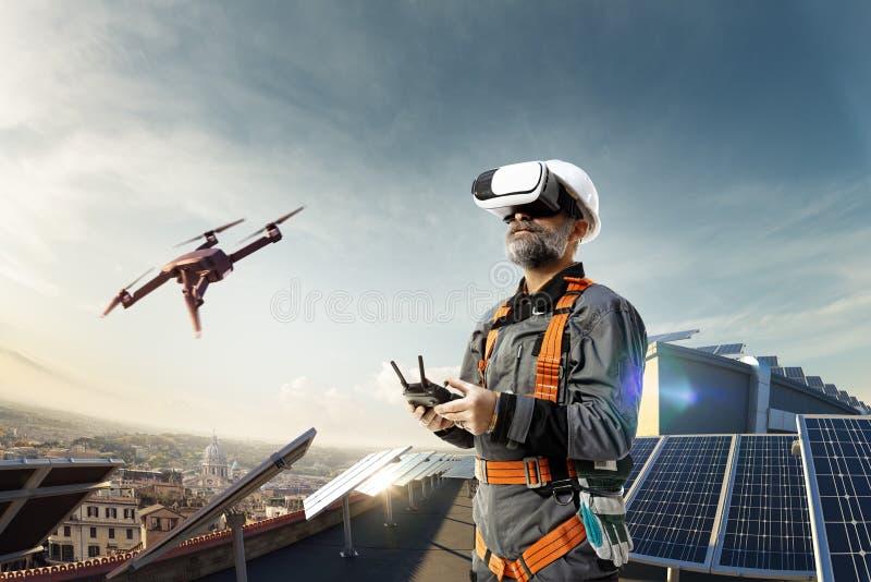 Ingegnere felice facendo uso del casco del vr e del fuco per cheking stazione solare in tetto fotografia stock