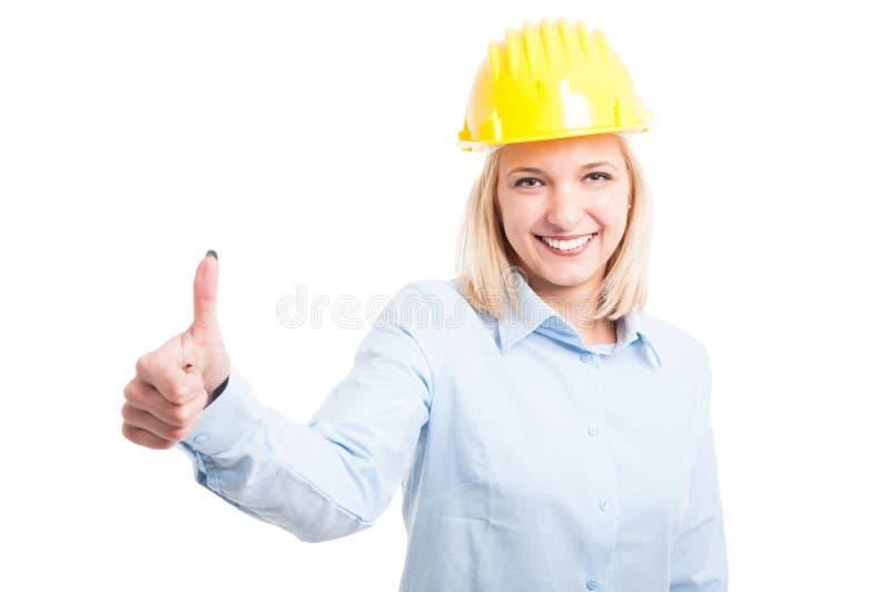 Ingegnere femminile che mostra come il gesto e sorridere immagine stock