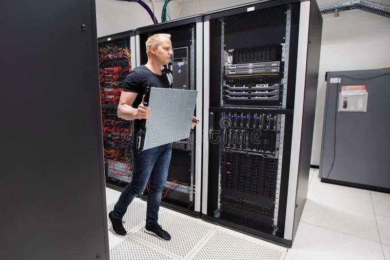 Ingegnere informatico Carrying Blade Server mentre camminando in Datacen immagini stock libere da diritti