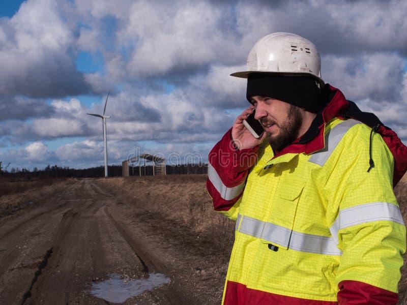 Ingegnere maschio in casco bianco che parla dal telefono moderno al campo con i piani che sviluppano i windmils immagini stock libere da diritti