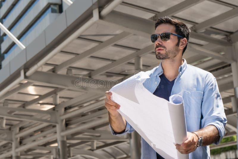 Ingegnere maschio che giudica piano di ingegneria a disposizione all'aperto a posizione della costruzione immagini stock libere da diritti