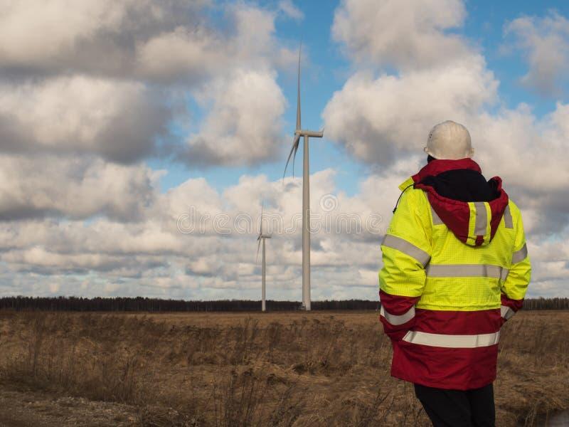 Ingegnere maschio dentro nel rivestimento di sicurezza ed in casco bianco, al campo con i piani che costruiscono i mulini a vento immagini stock libere da diritti