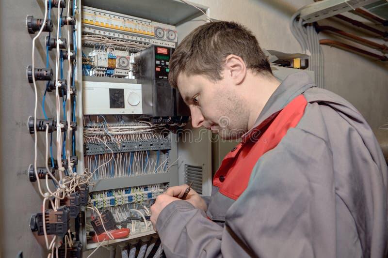 Ingegnere meccanico che fa switchboa elettrico dell'attrezzatura di aggiornamento fotografia stock libera da diritti