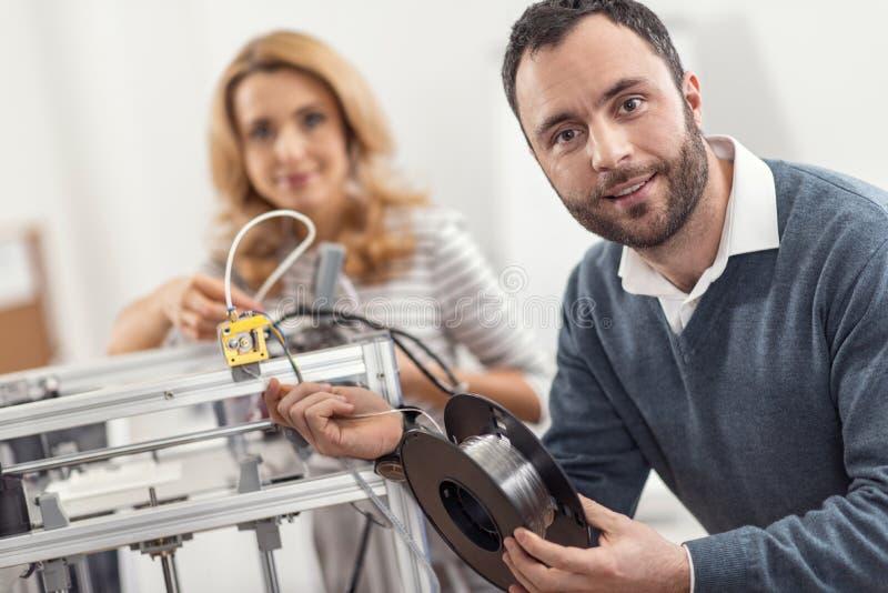 Ingegnere ottimistico che posa mentre sostituendo filamento in stampante 3D fotografie stock