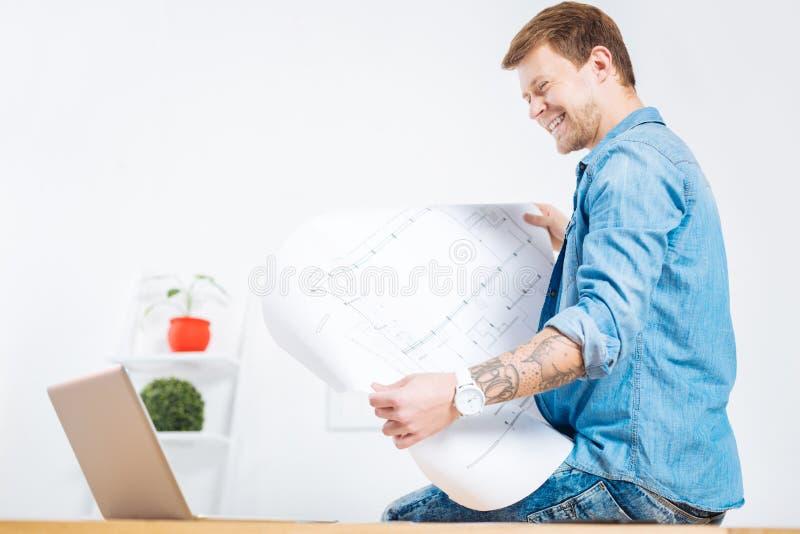Ingegnere positivo che sorride mentre esaminando il disegno immagine stock libera da diritti