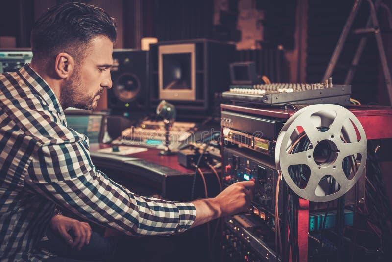 Ingegnere sano che lavora con l'audio attrezzatura professionale nello studio di registrazione fotografie stock libere da diritti