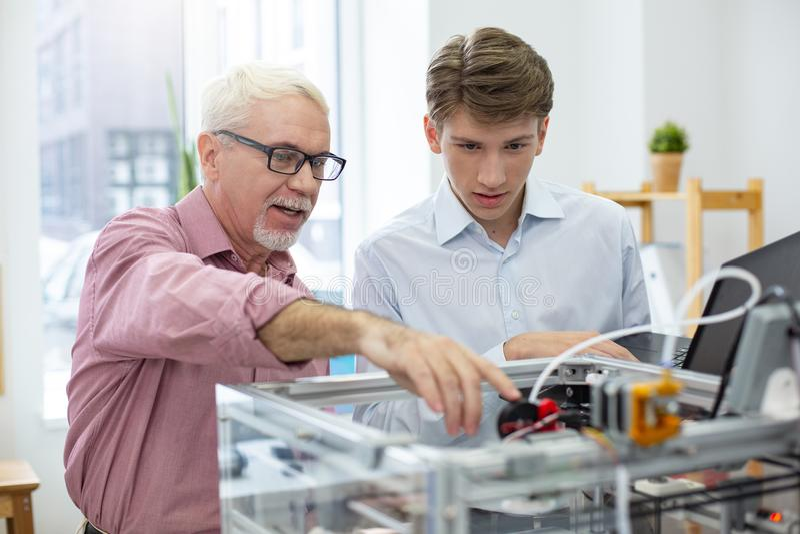 Ingegnere senior con esperienza che istruisce interno circa le stampanti 3D immagini stock
