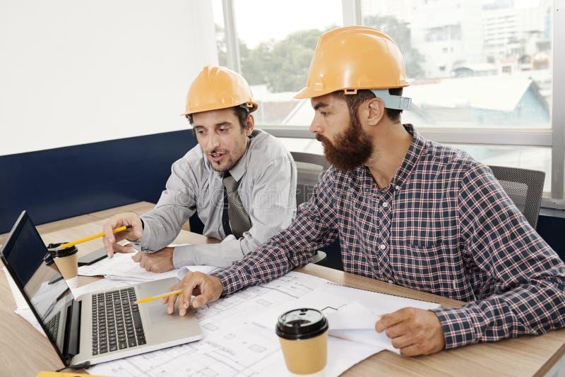Ingegneri che discutono progetto in schermo del computer portatile immagine stock