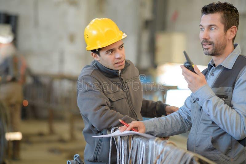 Ingegneri che lavorano in centrale elettrica che parla sul walkie-talkie fotografia stock libera da diritti