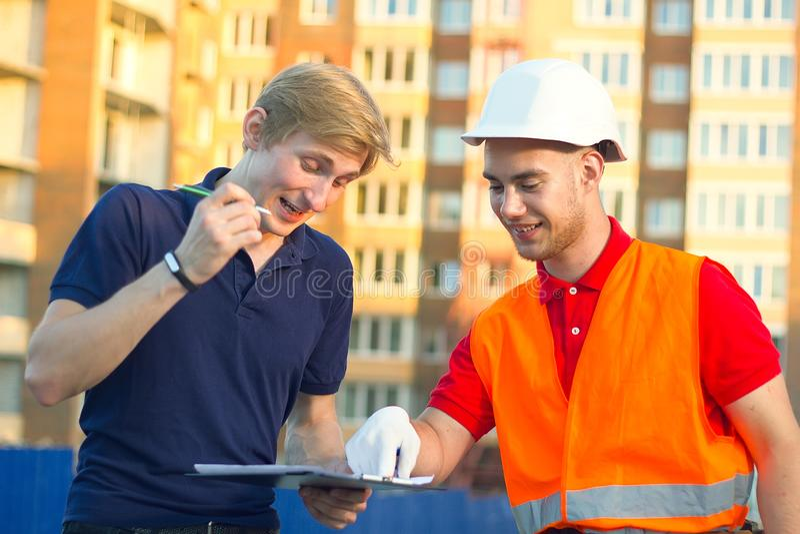 Ingegneri felici del costruttore in casco che fa segno alla lavagna per appunti immagine stock libera da diritti