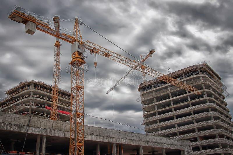 Ingegneria industriale Gru di costruzione sul cantiere contro lo sfondo di nuove costruzioni del bene immobile immagine stock libera da diritti