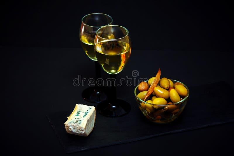Ingelegde groene olijven in een kom en witte wijn in een glas en een schimmelkaas stock foto's