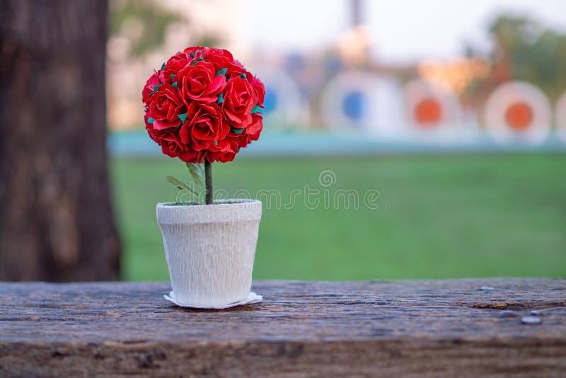 Ingemaakte rode rozen die op houten vloer en exemplaarruimte worden geplaatst De achtergrond is een tuin De rode rozen vervoeren  royalty-vrije stock afbeelding