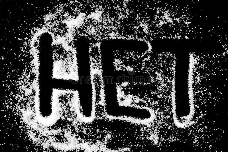 Ingen ordsymbolteckning vid fingret på vit saltar pulver på svart bakgrund royaltyfri bild