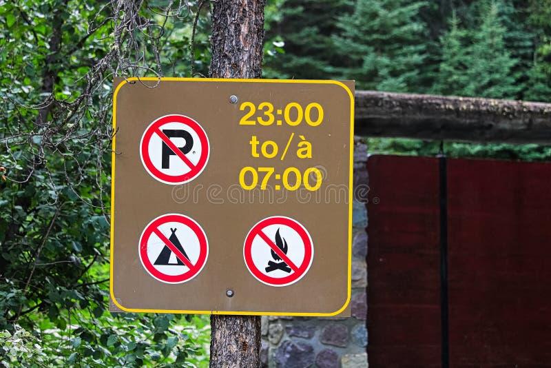 Ingen parkering, campa eller bränder under nattetidtecknet fotografering för bildbyråer