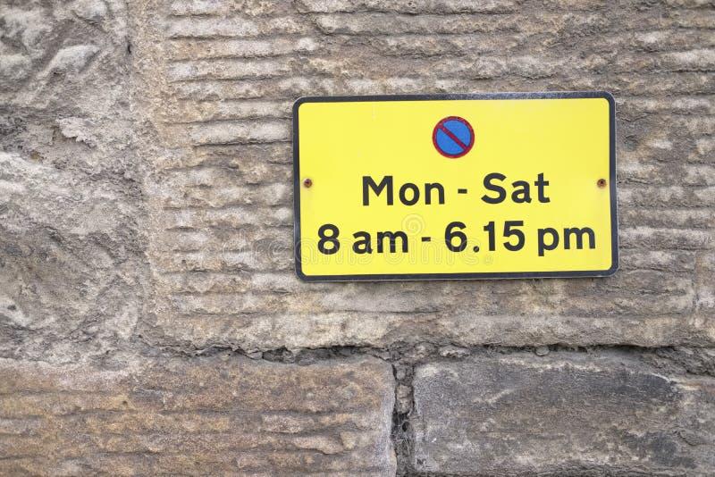 Ingen parkering måndag till suttna bilmedel under tecken för dagtidguling på väggen UK arkivbild