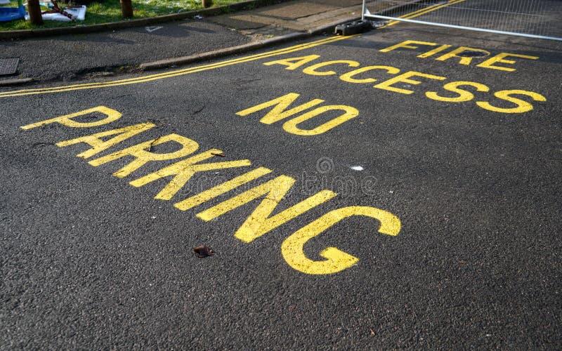Ingen parkering, tecken för brandtillträdestext med den dubbla gula linjen på asfaltvägen royaltyfri foto