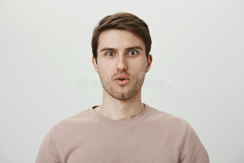 Ingen väg, är det hände egentligen Den häpna och chockade unga mannen med borstet i tillfälligt säga för sweater överraskar och a royaltyfria bilder