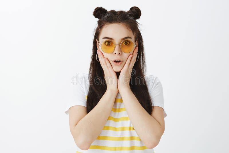 Ingen väg, vad ett rykte Stående av den chockade och fascinerade snygga flickan i gul solglasögon och t-skjorta som rymmer royaltyfria foton