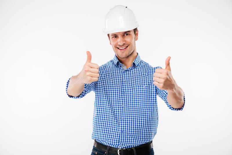Ingeniero alegre del hombre joven en el casco del edificio que muestra los pulgares para arriba imágenes de archivo libres de regalías