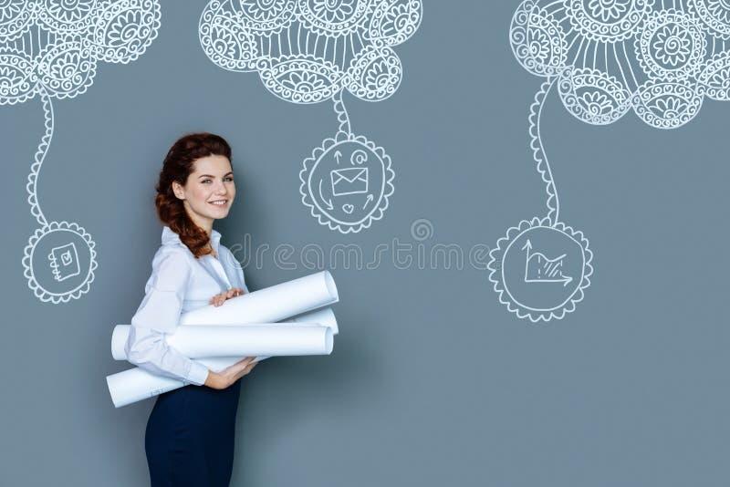 Ingeniero alegre que sonríe mientras que sostiene dibujos fotografía de archivo