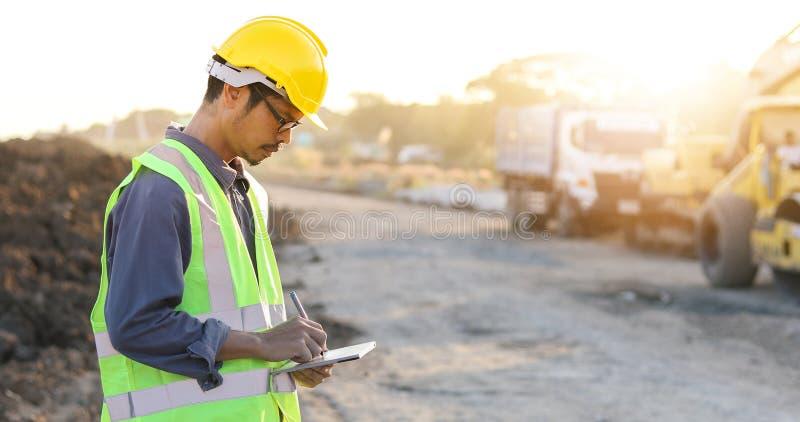 Ingeniero asiático con el casco de protección usando el ordenador de la PC de la tableta que examina y que trabaja en el emplazam imagenes de archivo
