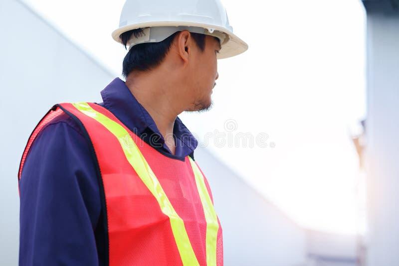 Ingeniero asiático en la seguridad uniforme y el casco blanco que da vuelta a la mirada en fondo borroso de la planta de la indus imagen de archivo libre de regalías