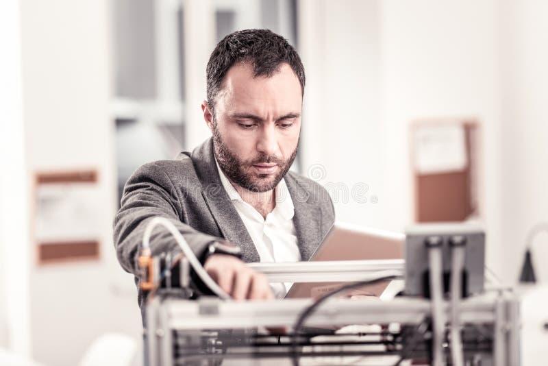 Ingeniero barbudo en la chaqueta que fija la impresora 3D imagen de archivo