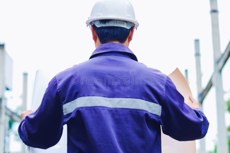 Ingeniero con el casco de seguridad blanco que lleva a cabo plan del proyecto en el fondo al aire libre del sitio de la construcc fotos de archivo