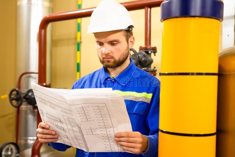 Ingeniero con el dibujo en fábrica del gas de poder y del combustible de aceite imagen de archivo libre de regalías
