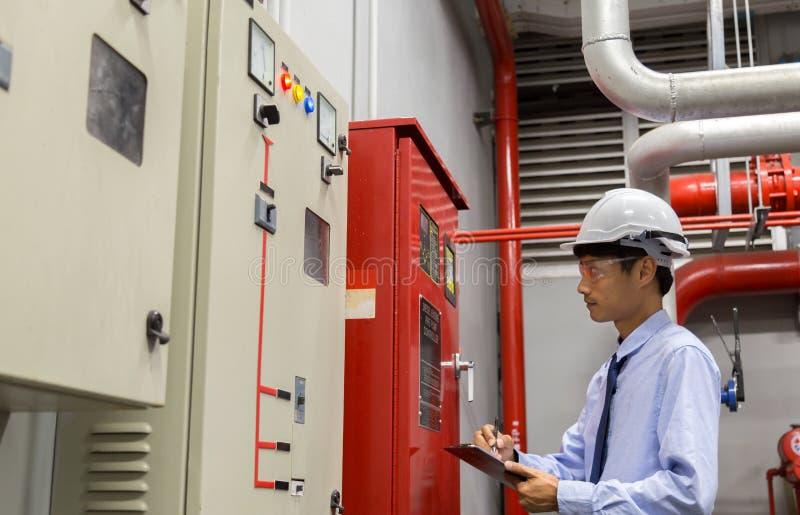 Ingeniero con la bomba roja del generador del control de la tableta para la tubería de la regadera del agua y el sistema de contr fotografía de archivo libre de regalías