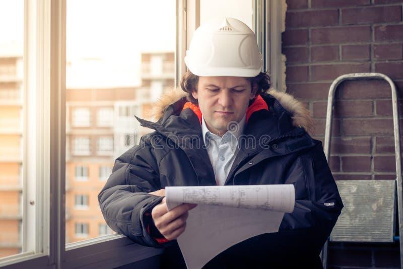 Ingeniero-constructor que trabaja con los documentos en el emplazamiento de la obra El trabajador examina dibujos en el emplazami imágenes de archivo libres de regalías