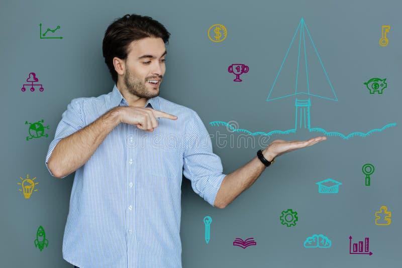 Ingeniero creativo que parece excitado mientras que señala a una miniatura del cohete imagenes de archivo