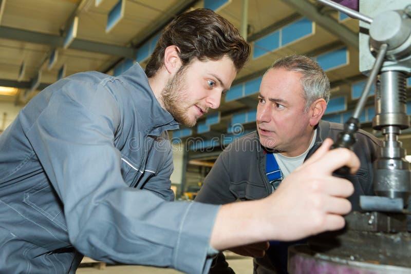 Ingeniero de aprendices trabajando en el piso de fábrica foto de archivo