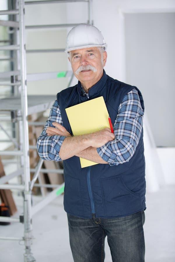 Ingeniero de construcción confiado en el casco de protección con los brazos cruzados foto de archivo
